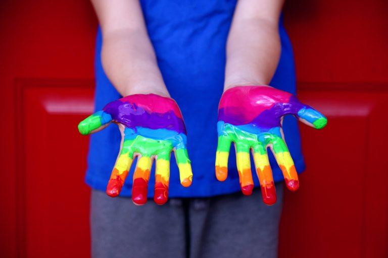 Mains couvertes de peinture arc-en-ciel