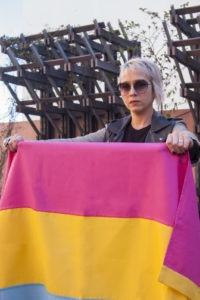 Personne pansexuelle tenant drapeau pansexuel