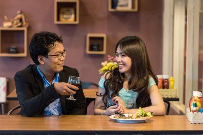 Deux adultes échangent autour d'un repas dans un restaurant