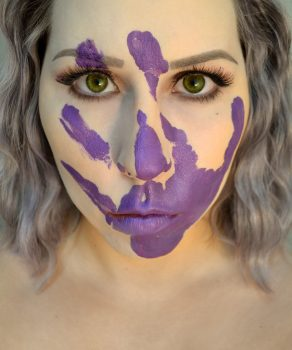 Femme visage couvert main mauve symbole lutte contre violences faites femmes
