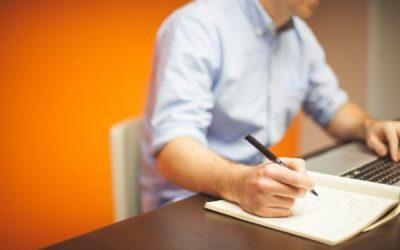 Homme assis ordinateur portable ecrit notes carnet