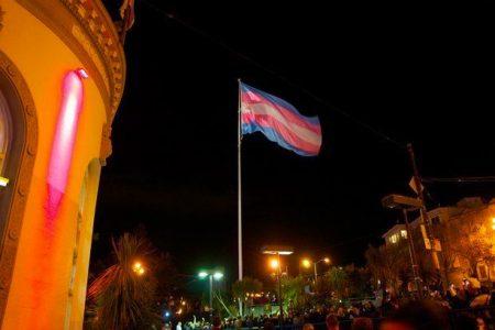 Photo de nuit du mat du Castro district de San Francisco avec le drapeau transgenre.