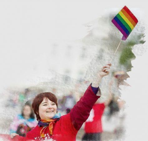 The Amber Heart : image femme tenant drapeau arc-en-ciel pour défendre droits personnes LGBTQI+